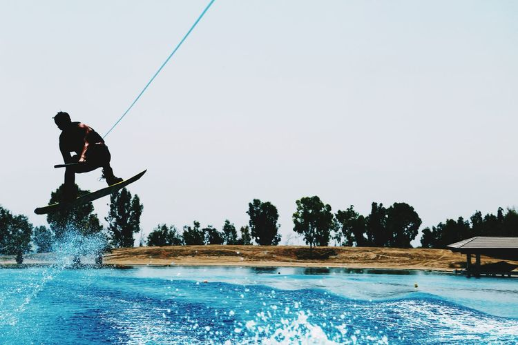 Silhouette man wakeboarding in sea against clear sky