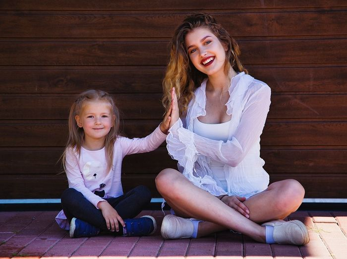 Portrait of happy mother and daughter sitting on wood