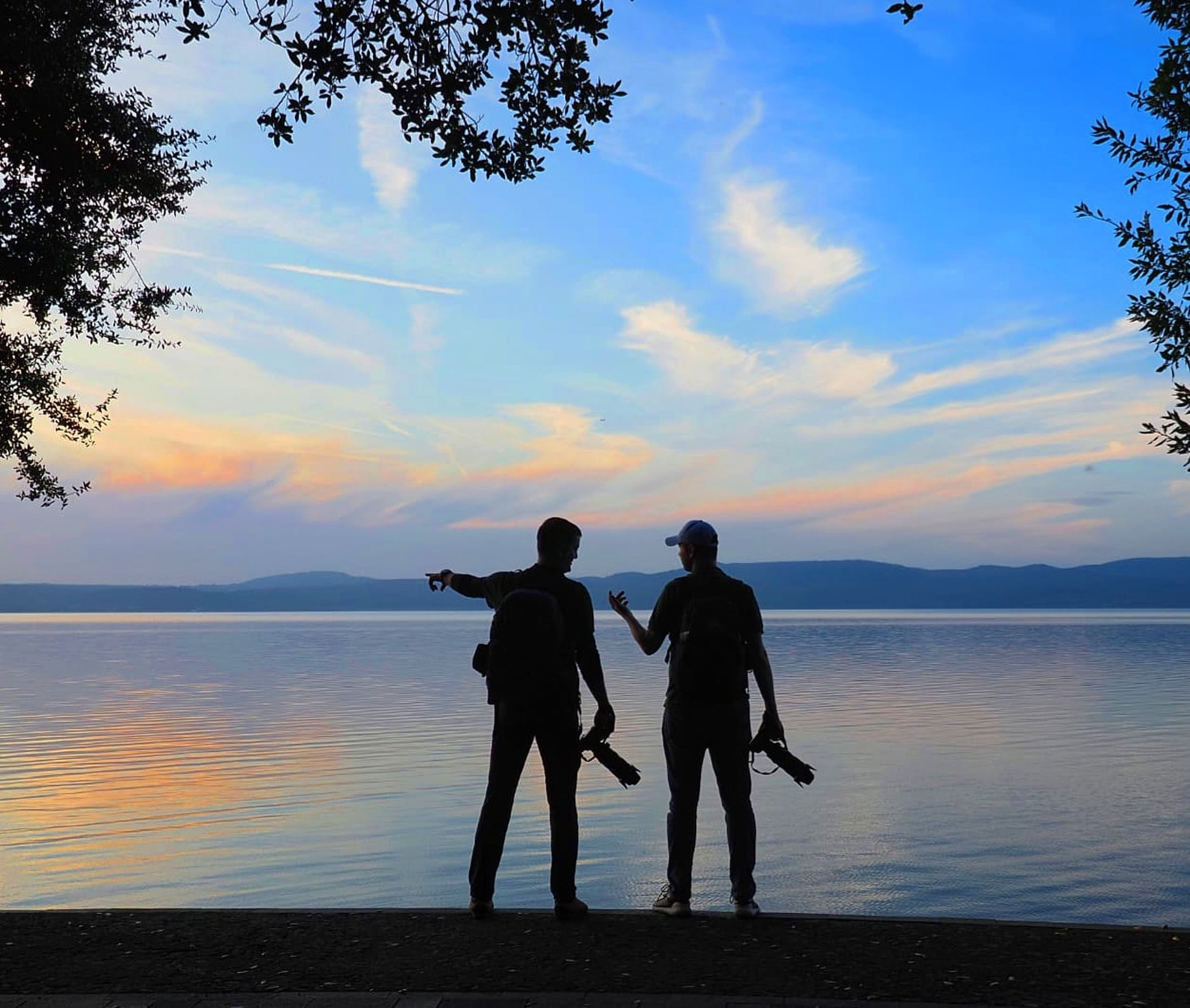 sky, water, real people, men, beauty in nature, standing, togetherness, lifestyles, cloud - sky, scenics - nature, silhouette, full length, leisure activity, two people, nature, lake, bonding, people, sunset, positive emotion, outdoors, couple - relationship