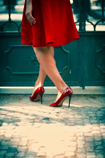Low section of woman wearing red high heels while walking on footpath