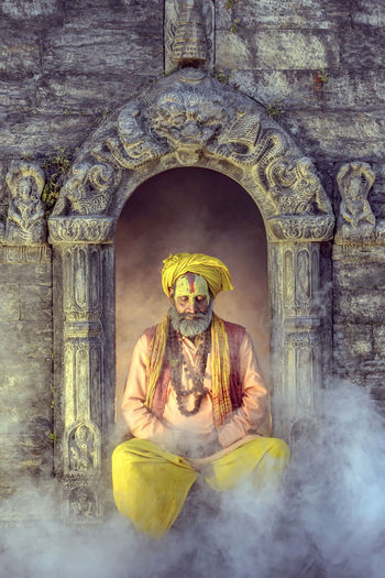Sadhu sitting amidst smoke against built structure