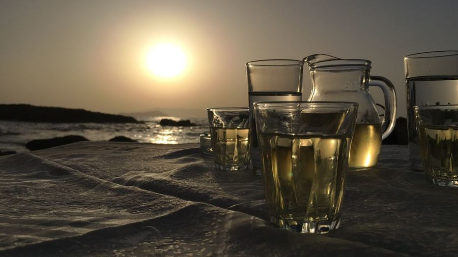 Close-up of beer in sea against sky during sunset