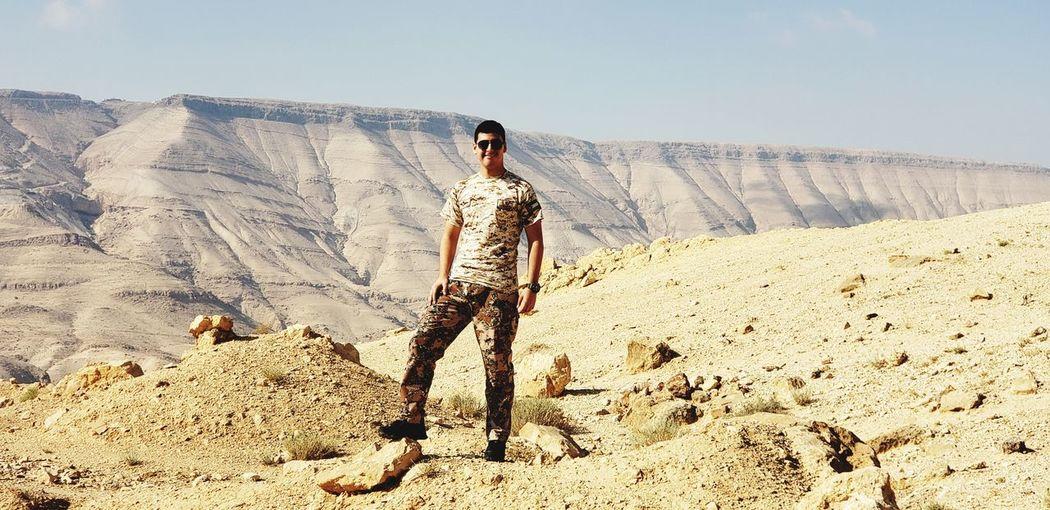 Full length of man standing on rocky mountain