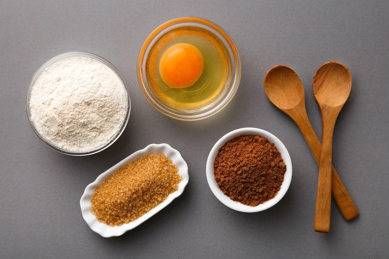 Baking ingredients flat lay (flour, egg, cocoa, sugar. spoons). Top view Baking Baking Ingredients Bowl Bowls Brown Sugar Cocoa Egg Food Ingredients No People Spoons Sugar Wooden Spoons Yolk