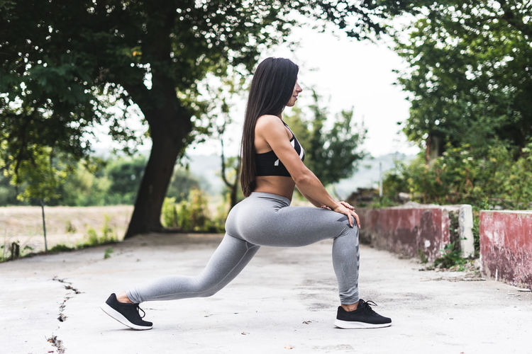 Woman exercising on footpath against trees