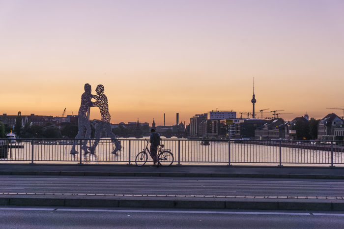 Spree River with Molecule Men and TV Tower Berlin Elsen Bridge Germany 🇩🇪 Deutschland Molecule Men Spree River Berlin TV Tower Architecture Bridge - Man Made Structure Building Exterior Built Structure City Cityscape Color Image Full Length Leisure Activity Lifestyles Men Outdoors Railing Real People Sky Sunset Travel Destinations Urban Skyline Water