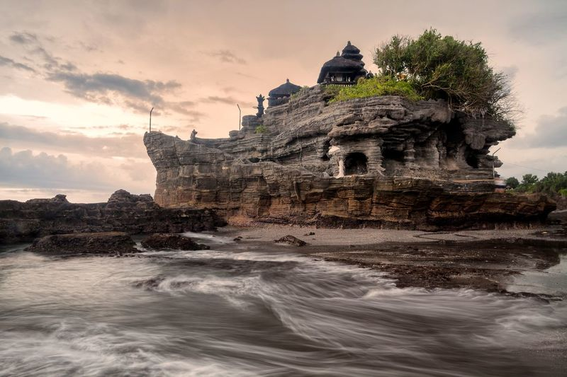 View of tanah lot rock formation against cloudy sky