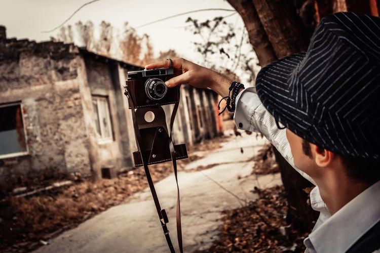 Close-up of man taking selfie with analog photo camera.