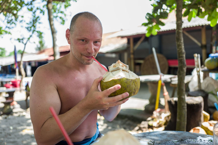Caucasian man drinking a coconut in Canggu Adult Day Focus On Foreground Food And Drink Front View Holding Leisure Activity Lifestyles Looking At Camera Males  Men Nature One Person Outdoors Portrait Real People Shirtless Young Adult Young Men