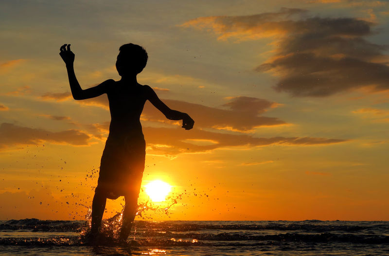 Low angle view of silhouette boy splashing water in sea
