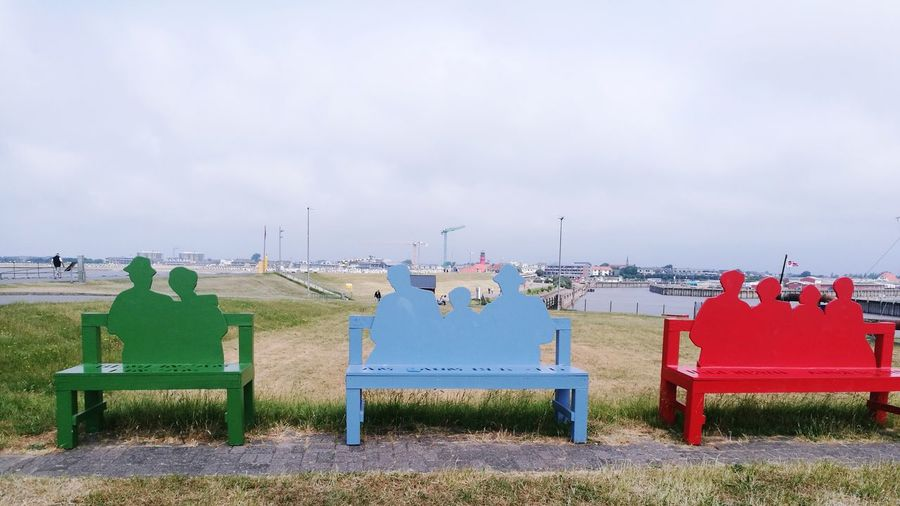 Colorful empty benches on land against sky