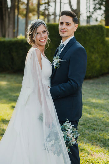 Portrait of bride and groom standing on grass in park
