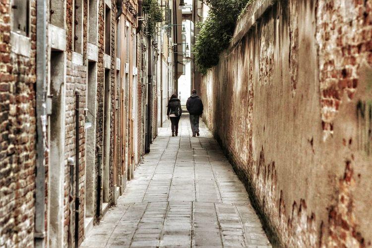Full length rear view of people walking on footpath amidst buildings in city