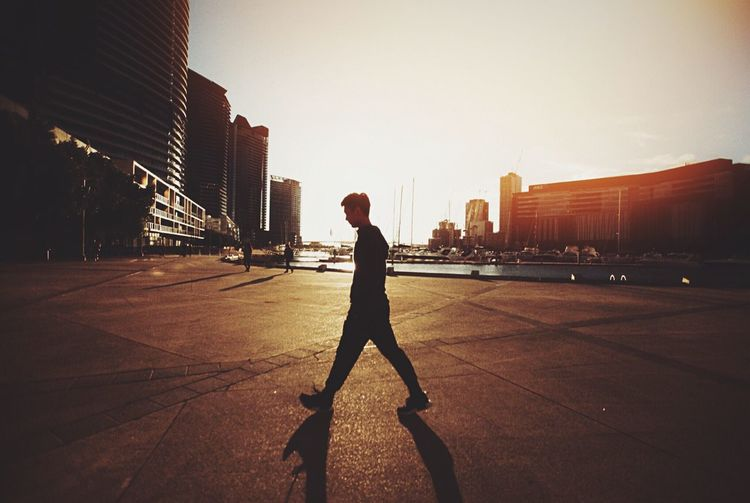 Side View Of Man Walking On Street In City Against Sky During Sunset