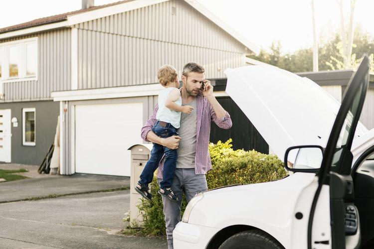 Full length of boy standing in car