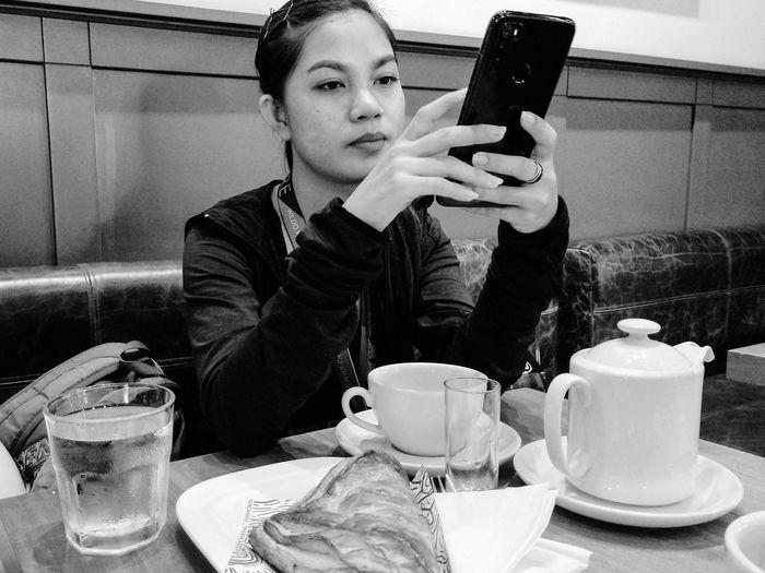 Mid adult man using smart phone in restaurant