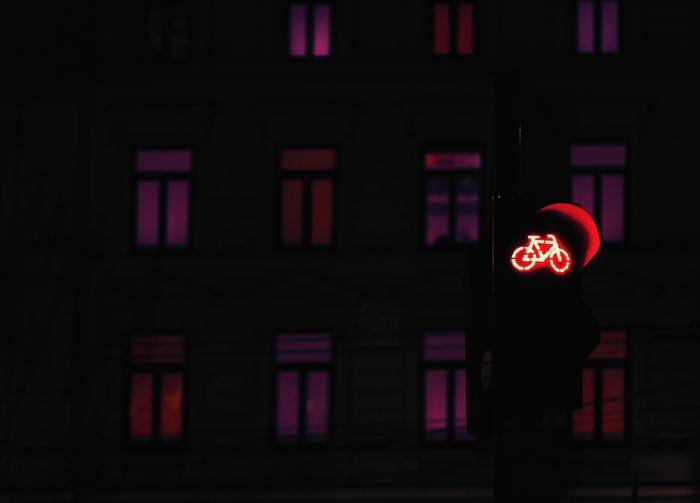 Low angle view of illuminated road signal at night