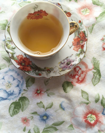 Cup of tea on floral fabric Cloth Cup And Saucer Cup Of Tea..  Dishware Drink Fabric Feminine  Floral Floral Patterns Girly Indoors  Liquid Natural Light Nobody Nostalgic  Overhead Phone Camera Pretty Refreshing Beverage Romantic Textures