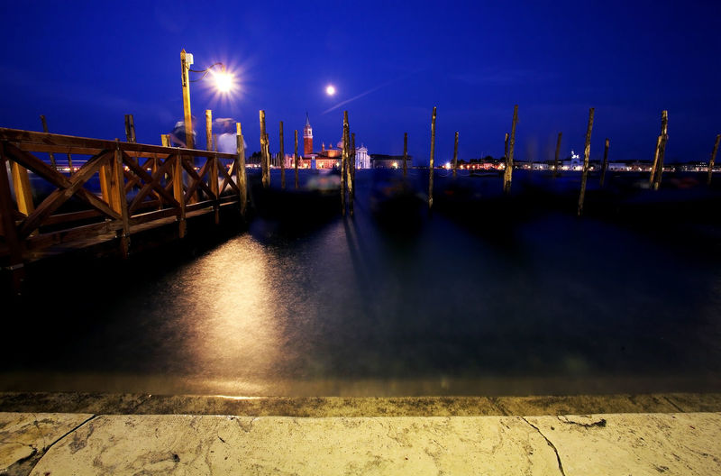 Pier over grand canal by illuminated street light against sky at night