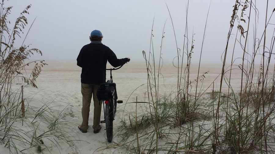 Rear view of man with bicycle at beach