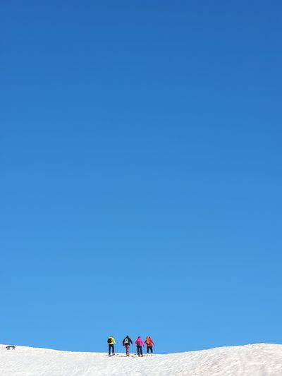 People standing against clear blue sky