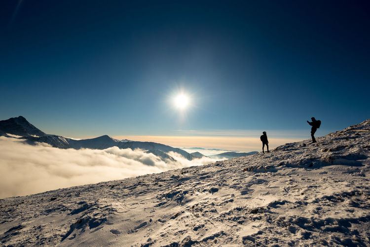 People on snowcapped mountain against sky during winter