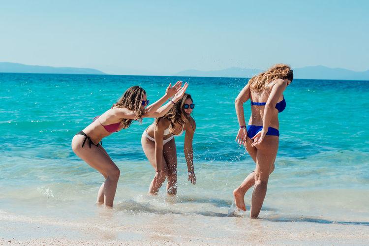 Female Friends In Bikini Smiling On Shore