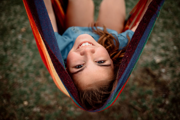 High angle portrait of smiling girl lying on hammock