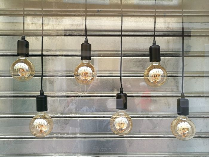 Close-Up Of Light Bulbs Hanging Against Wall