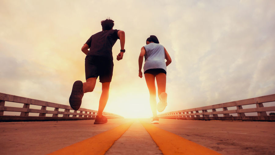 Two runners ran outside. And running on jogging roads. The concept of creating good health Sky Sunset Lifestyles Rear View Nature Leisure Activity Full Length Sunlight Real People Men Two People Women Adult Beauty In Nature Architecture People Sun Togetherness Cloud - Sky Orange Color Outdoors Shorts Couple - Relationship
