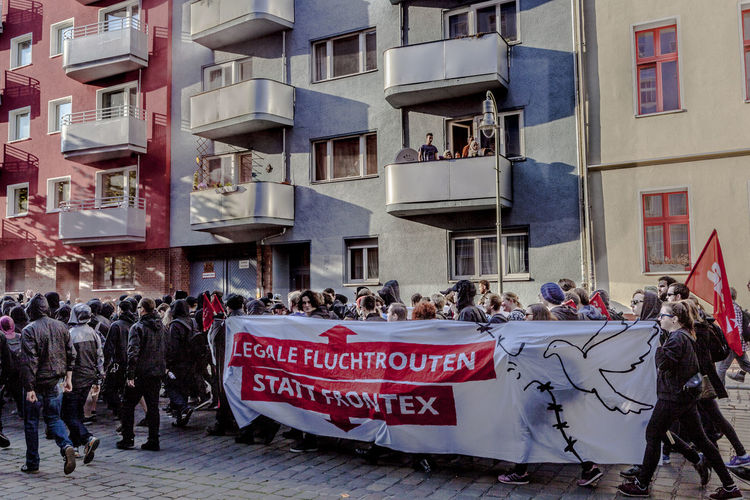 Crowd walking on street by buildings at may day