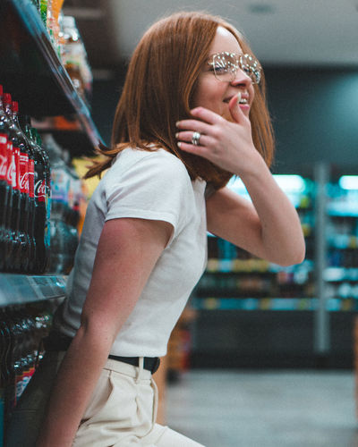 Real People Women Focus On Foreground Leisure Activity Glasses Lifestyles One Person Happiness Emotion Casual Clothing Young Women Young Adult Adult Hairstyle Side View Retail  Three Quarter Length Fashion Standing Excitement Bokeh Bokeh Photography Store Redhead Portrait Portrait Photography Grocery Store