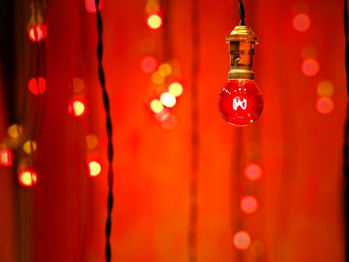 Close-up of red illuminated light bulb in room