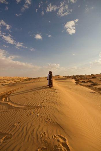 Men standing in arid landscape against sky on sunny day