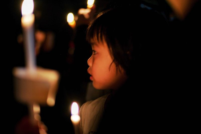 A girl with lighting candles in a night of condolence and sympathy Commemorative Missing Lost Pass Away Lighting Candle Sadness Condolence Headshot One Person Burning Night Fire Portrait Illuminated Adult Candle Lifestyles Human Face Dark Flame