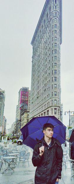 Man holding umbrella standing against flatiron building in city