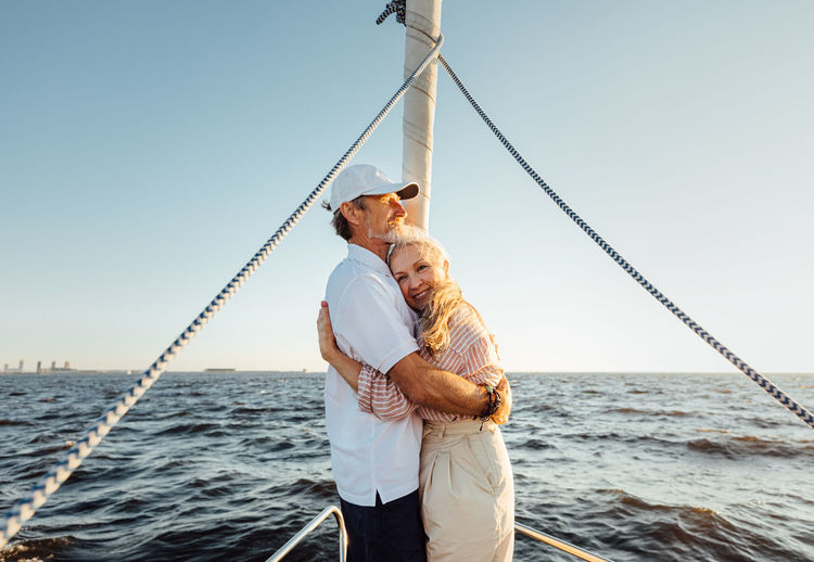 Senior couple embracing while standing on boat against sea