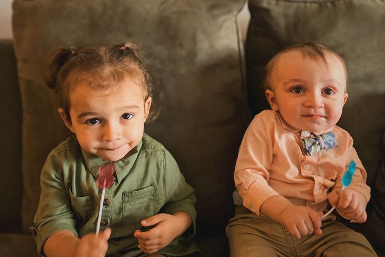 Cute siblings eating candy while sitting on sofa at home