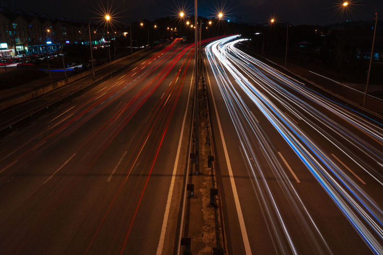 Lightrail of vehicle passing at higway during nightfall Capture Tomorrow
