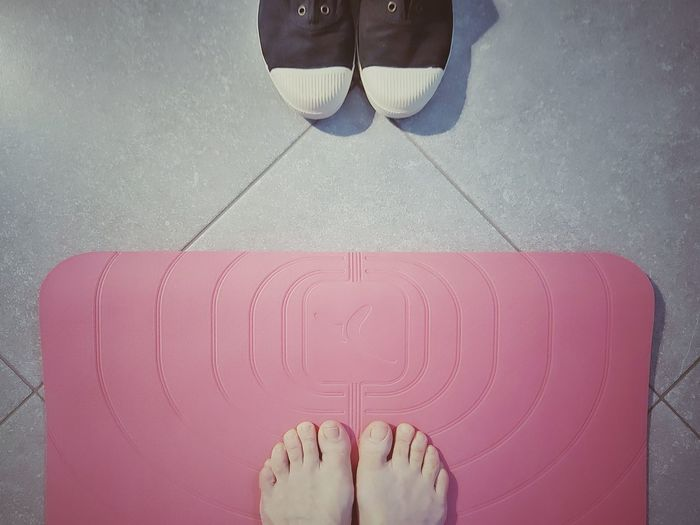Low section of woman standing on tiled floor