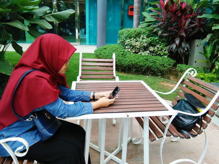 Side view of woman wearing hijab using smart phone while sitting outdoors