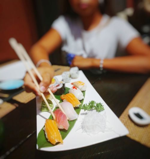 Midsection of man holding sushi on table in restaurant