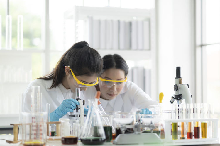 Two scientists performing experiment in laboratory