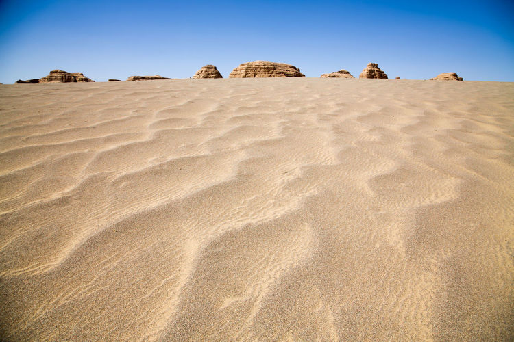 Low angle view of sand dune against clear sky