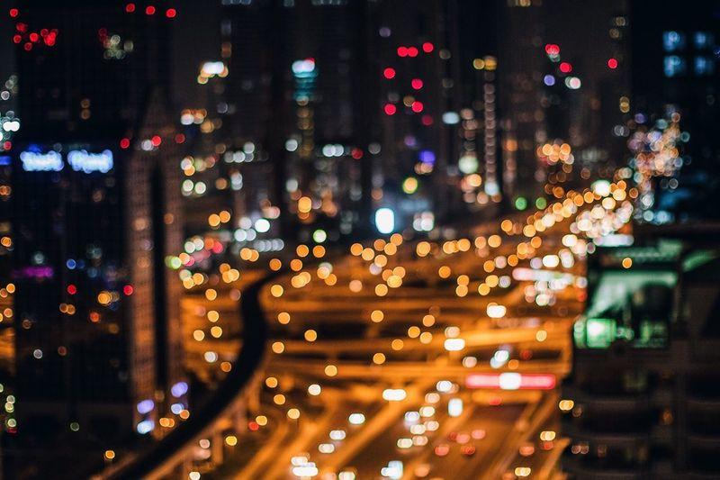 Defocused Image Of Illuminated Cityscape At Night