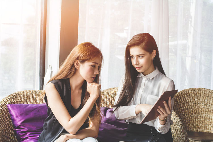 Young Asian. women Business people meeting point to discuss, plan. Trading of economic cosmetics.With sunset light Business Discussing Meeting Plane Adult Beautiful Woman Casual Clothing Cosmetics Economic Hairstyle Indoors  People Point Real People Redhead Sitting Togetherness Trading Online Two People Waist Up Window Wireless Technology Women Young Adult Young Women