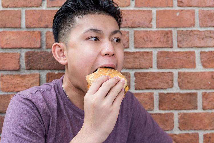 Portrait of boy eating food against brick wall