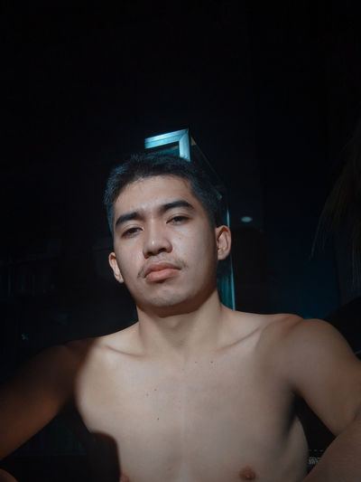 Portrait of shirtless young man sitting at home