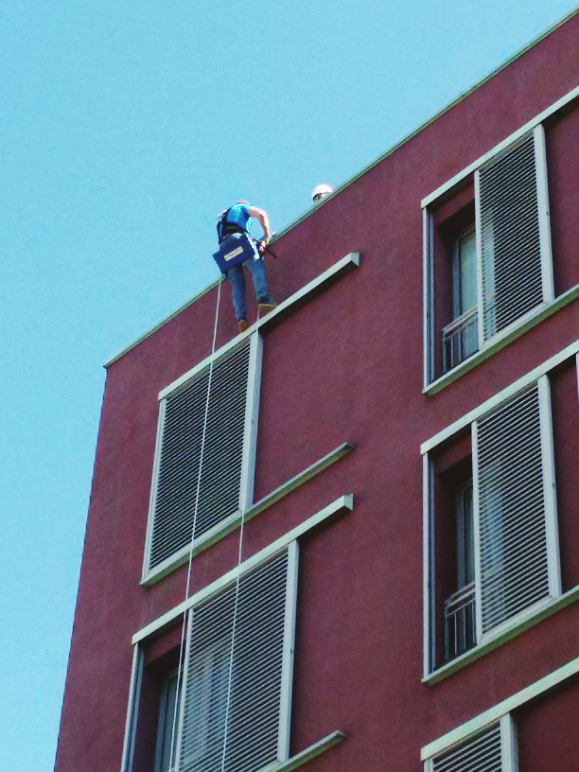 low angle view, architecture, building exterior, window, built structure, clear sky, day, outdoors, window washer, one person, occupation, men, real people, manual worker, sky, people
