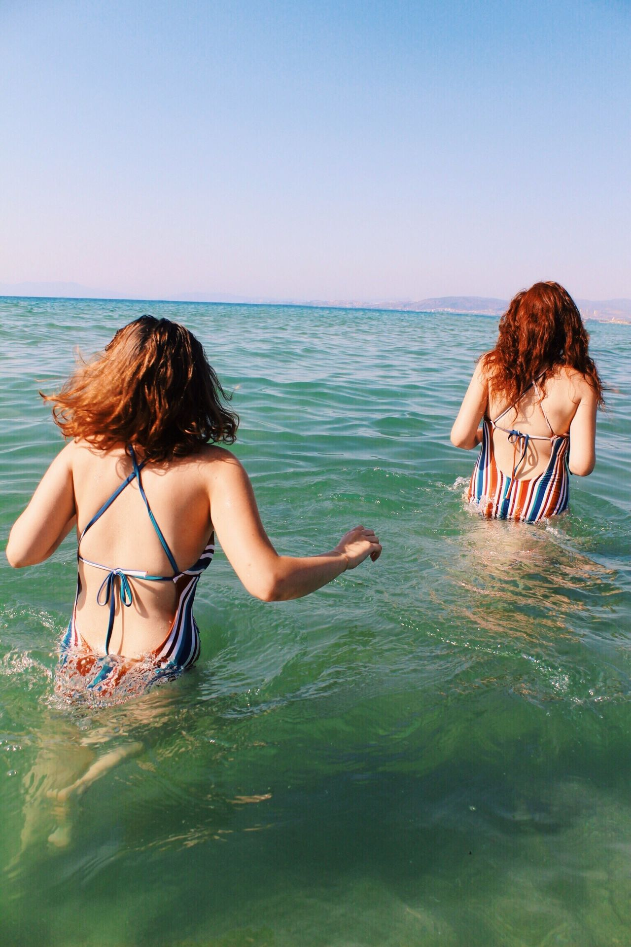 Rear view of young women wading into water